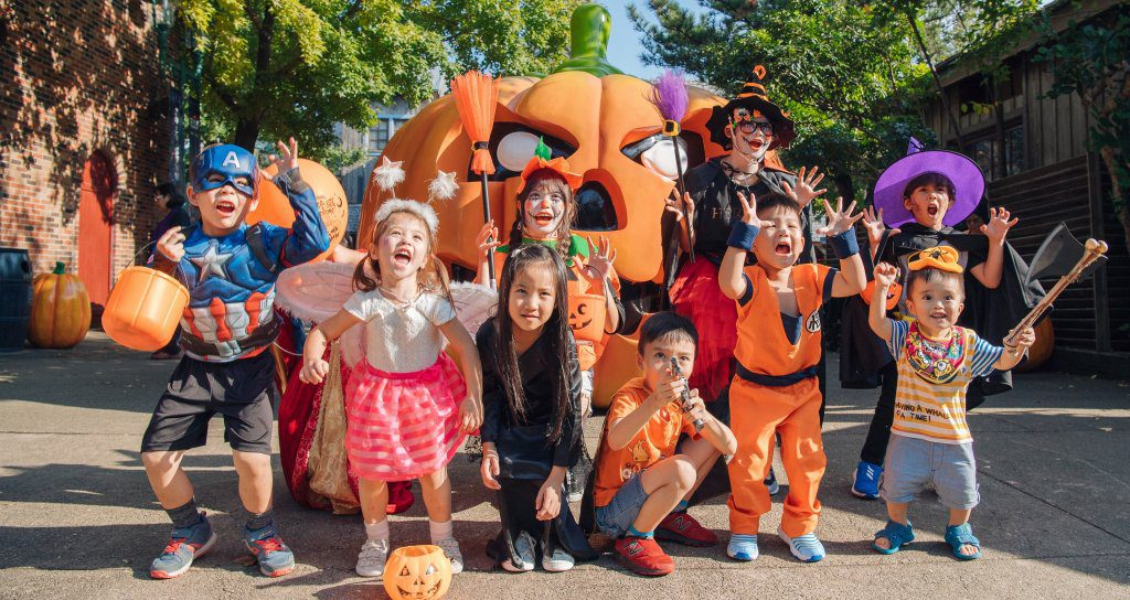 There are many children dressed in different Halloween costumes.